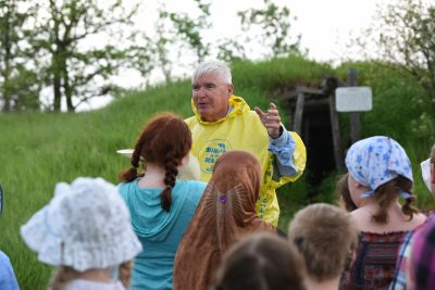 Volunteer site interpreter speaks with youth about the 1850s in Minnesota
